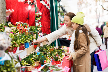 Happy woman with little daughter  buying floral composition