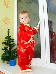 Serious little boy in Chinese holiday costume stands on the sill