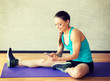 smiling woman stretching leg on mat in gym