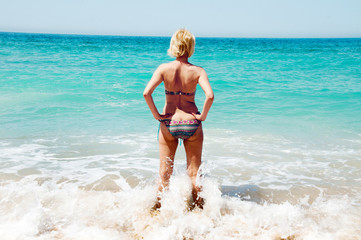 woman is standing and looking at the sea
