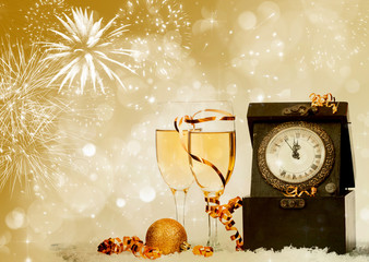 Champagne against fireworks, clock close to midnight and sparkli