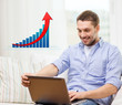 smiling man with laptop and growth chart at home