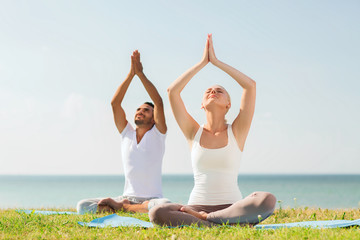 smiling couple making yoga exercises outdoors