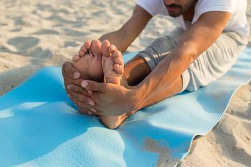 close up of man making yoga exercises outdoors