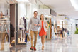 happy young couple with shopping bags in mall - 74967004