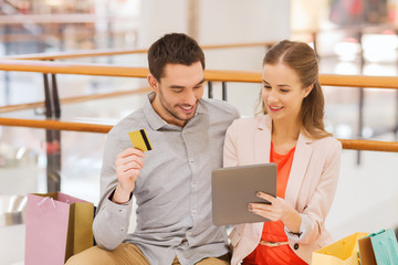 couple with tablet pc and credit card in mall