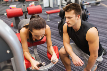 young woman with trainer exercising on gym machine