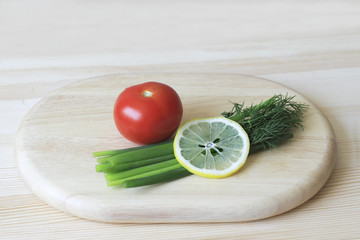 Red tomato, green onion, dill, lemon on a cutting Board