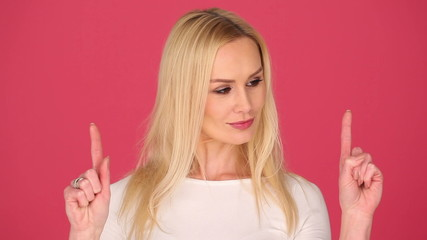 blonde attractive woman on pink background showing space