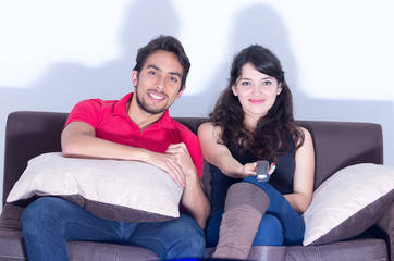 young attractive couple watching movie at home
