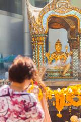 Woman tourist praying at Erawan Shrine