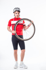 Young man in cycling outfit  with bike wheel