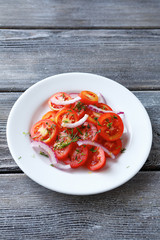 Tomatoes and onions on a white plate