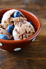 Sweet ice cream with blueberries in deep bowl