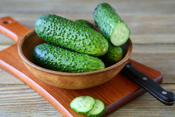 Cucumbers in a bowl on cutting board
