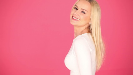 Attractive woman with a lovely smile wearing white on the pink