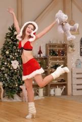 Santa girl in Christmas costume jumps with cute teddy bear