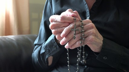 Senior Woman Praying with Rosary and Crucifix in her Old Hands