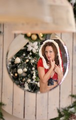 Beautiful young woman in Santa Claus clothes looking in mirror