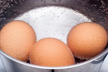 eggs boiling in pan of water