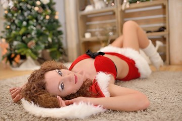 Beautiful sexy girl in Santa Claus clothes posing on warm rug