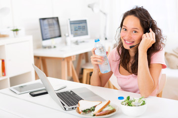 Young attractive student drinking water while working