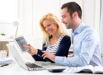 Young attractive couple using tablet at home