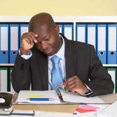 Afrikanischer Geschäftsmann im Büro ist gestresst