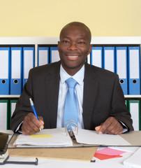 Lachender afrikanischer Geschäftsmann im Büro