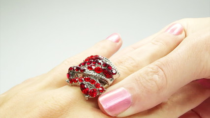 jewelery ring with red ruby crystals putting on the finger