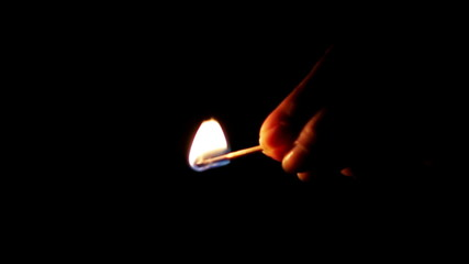 Burning match in woman's hand on black background