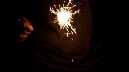 Burning sparkler in the woman's hand on a black background