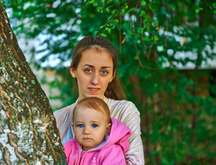 Blue-eyed little girl with his young mother outdoor