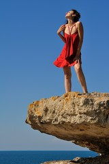 Beautiful girl in relax on rock with blue sky