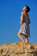 Beautiful girl in relaxi on rock with blue sky