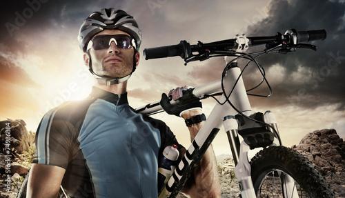 Sport. Cyclist carry a bike on dramatic sky.