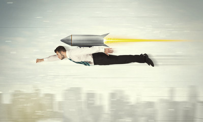 Superhero business man flying with jet pack rocket above the cit