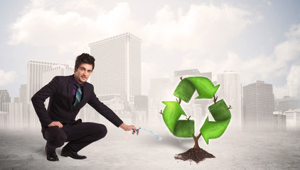 Business man watering green recycle sign tree on city background