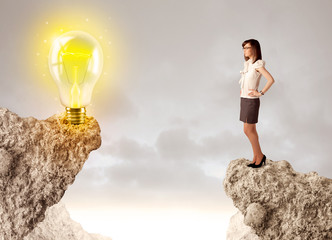 Businesswoman on rock mountain with idea bulb