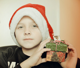 child in Santa hat and present in his hands