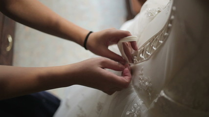 Lacing up a corset of a wedding dress