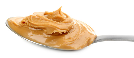 Creamy peanut butter in spoon, isolated on white