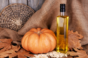 Pumpkin seed oil in glass bottle and fresh pumpkin