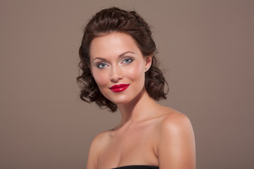 Young brunette woman with bright lipstick and curly hair