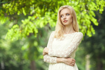 Beautiful young blond woman in a white dress