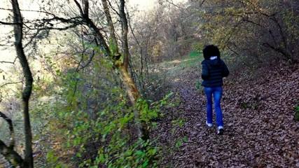 Girl runs through the park forest in autumn