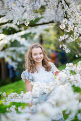 Beautiful young girl in cherry blossom garden