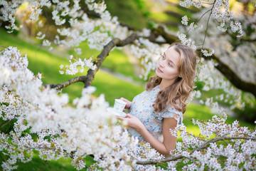 Girl drinking tea in cherry blossom garden