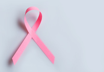 Pink breast cancer ribbon on grey background