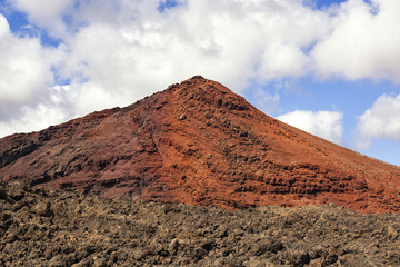 Red volcano with solidified lava in the foreground